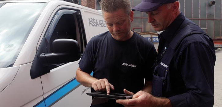 Two ASSA ABLOY employees look at a tablet while standing next to a company vehicle