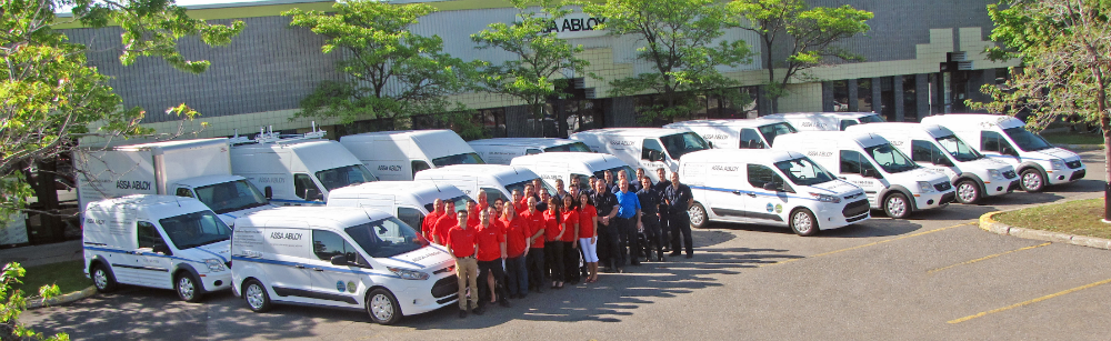 Photo of the ASSA ABLOY team in front of company vehicles